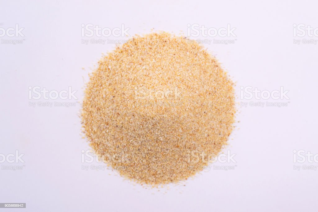 A pile of granulated garlic powder isolated on white background stock photo