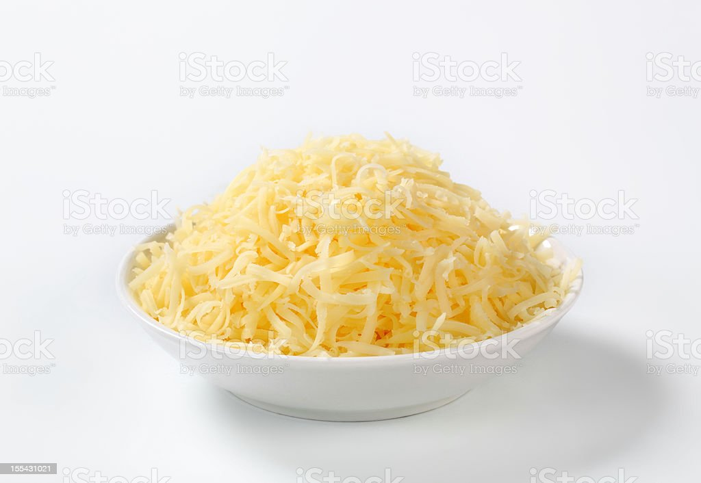 A pile of grated cheese in a white bowl on white background stock photo