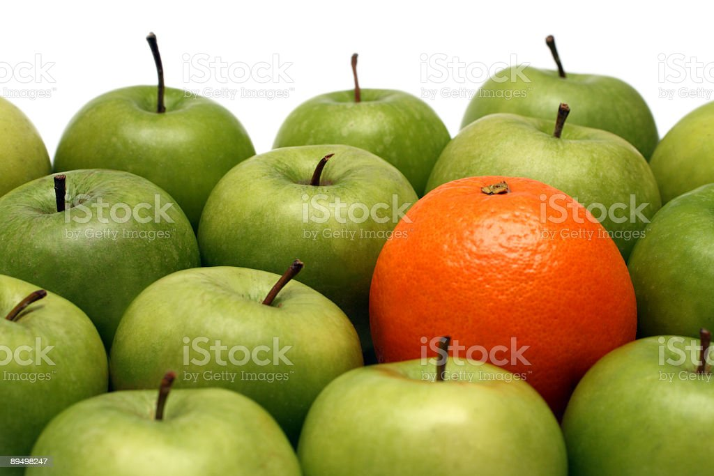 A pile of green apples and one orange stock photo