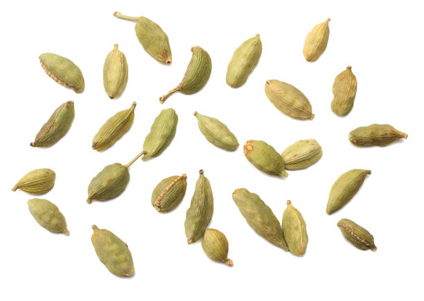 Pile of green Cardamom, cardamon or cardamum (dried fruits of Elettaria cardamomum) isolated on white. shadow separated top view Pile of green Cardamom, cardamon or cardamum (dried fruits of Elettaria cardamomum) isolated on white. shadow separated top view cardamom stock pictures, royalty-free photos & images