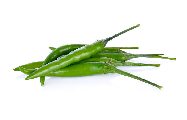 pile of green chili with stem on white background - green chilli pepper stock photos and pictures