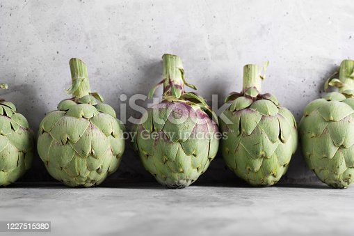 Pile of green Spanish or Italian Artichokes on the gray concrete background
