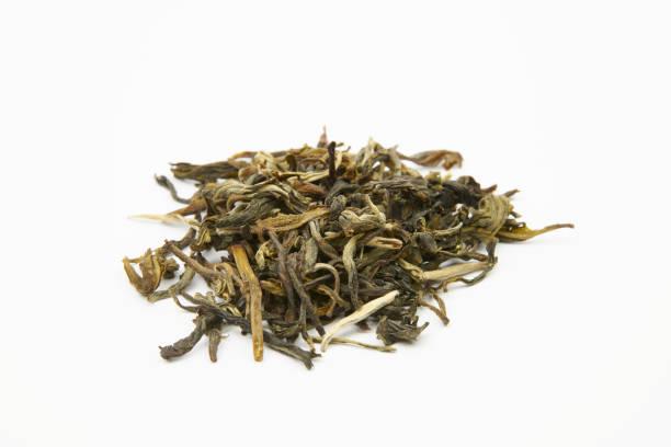 haufen von grünem tee blätter auf einem weißen hintergrund - china jade snow - grüner tee koffein stock-fotos und bilder