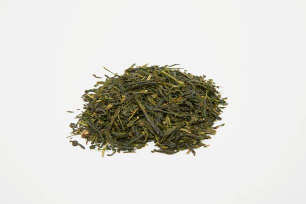 haufen von grünem tee blätter auf einem weißen hintergrund - japan gyokuro - grüner tee koffein stock-fotos und bilder