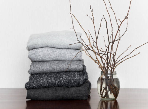 pile of grey knitted sweaters and a vase with branches - caxemira imagens e fotografias de stock