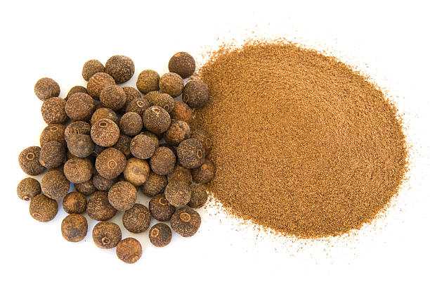 Pile of ground and whole allspice on white  allspice stock pictures, royalty-free photos & images