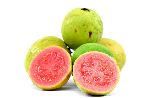 Pile of guavas with a cut open guava in front  Fresh Guavas fruit over white background . guava stock pictures, royalty-free photos & images