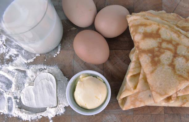 pila de panqueques franceses caseros con un corazón en harina, huevos y mantequilla en una tabla - foto de stock