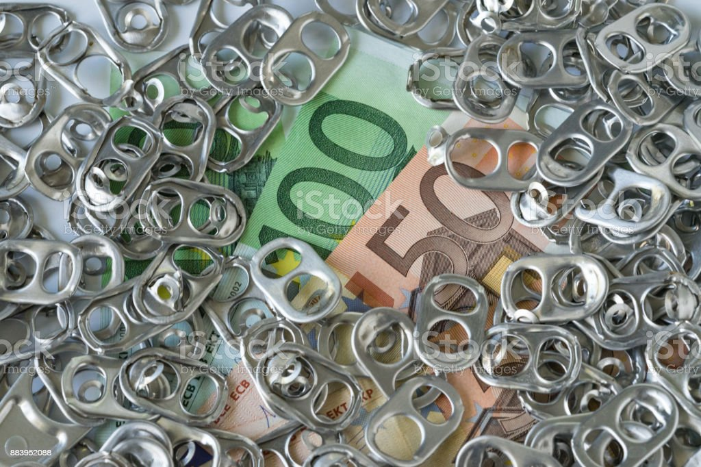 Pile of hoop can opener or pull ring on money banknotes as rich eco recycle or green world concept stock photo