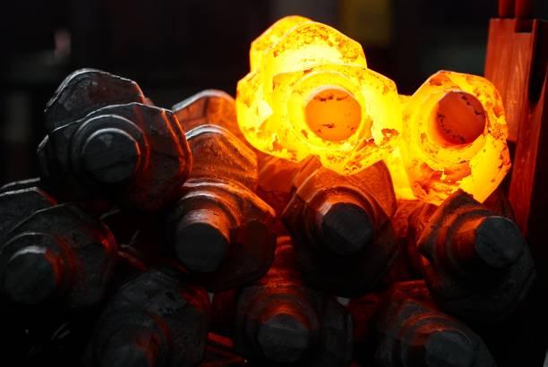 pile of hot steel parts. crankshaft production stock photo