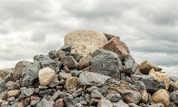 pile of huge rocks and boulders under dark grey sky - stack rock stock pictures, royalty-free photos & images