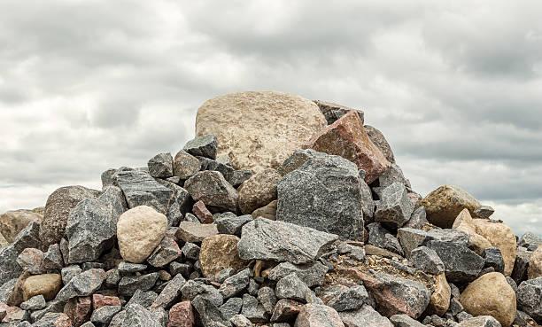 pile of huge rocks and boulders under dark grey sky - boulder rock stock pictures, royalty-free photos & images