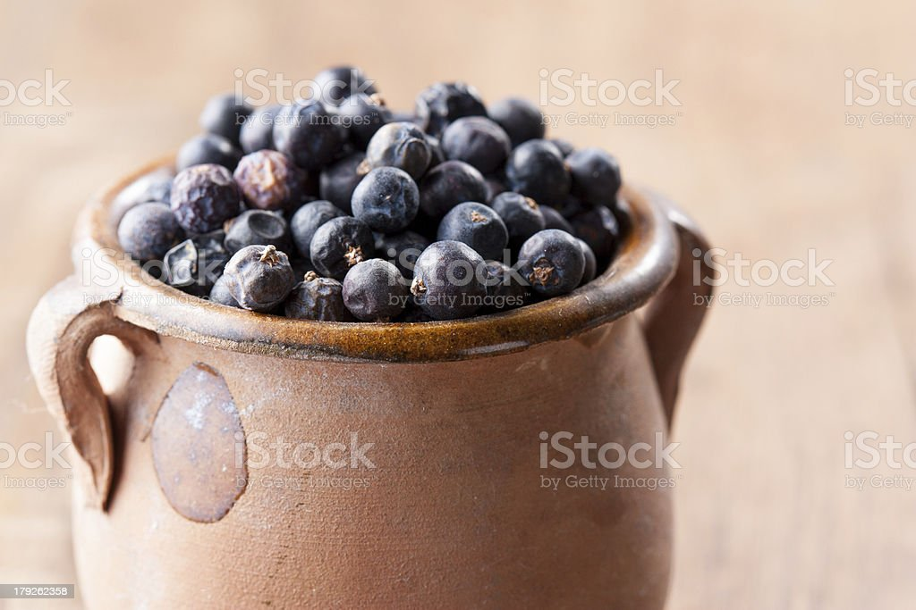 Pile of juniper berries on ceramic bowl stock photo