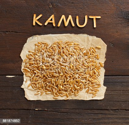 Pile of Kamut grain on wooden background top view