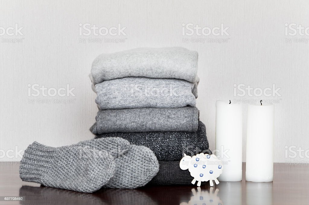 Pile of knitted sweaters and mittens decorated with candles stock photo