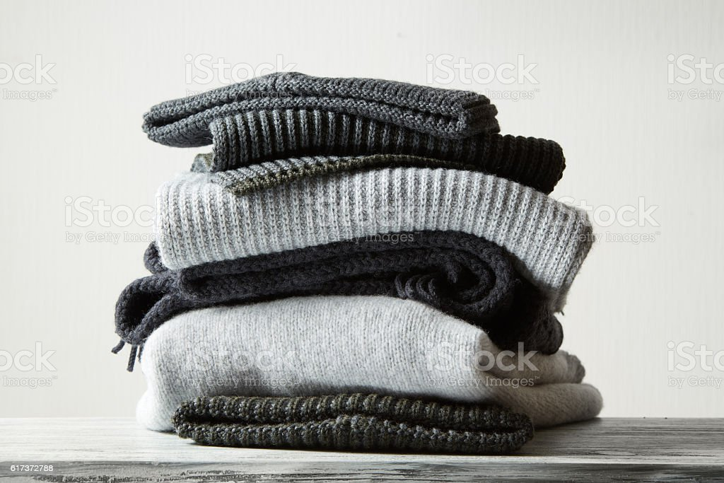 Pile of knitted winter clothes on background stock photo