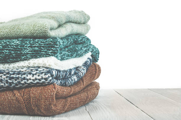 Pile of knitted winter clothes on wooden background, sweaters, k stock photo