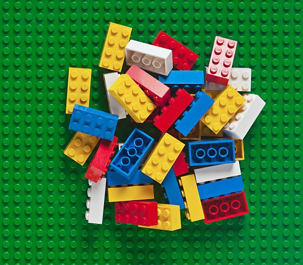 pile of lego block bricks on green baseplate - lego stockfoto's en -beelden