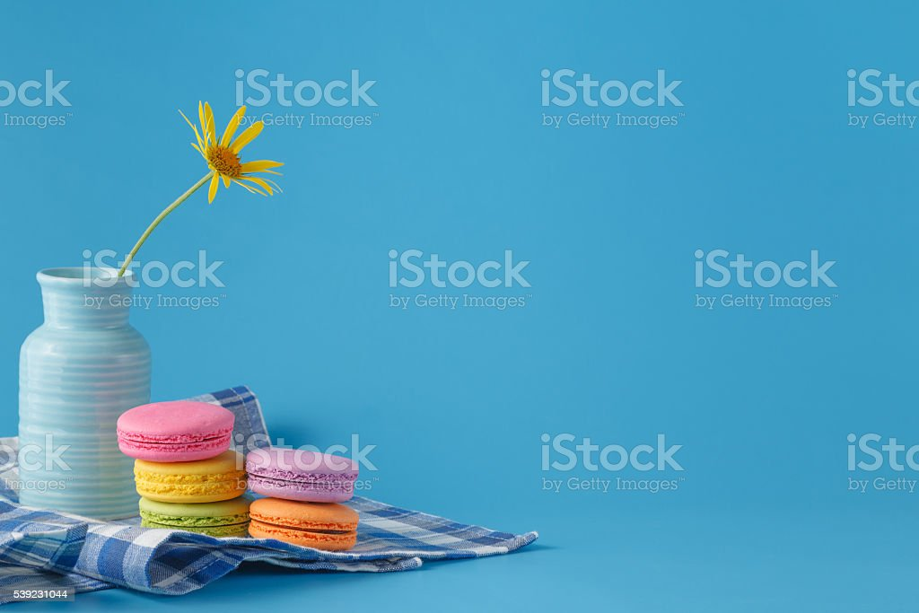 Pile of macaroons and yellow flower with copy space royalty-free stock photo