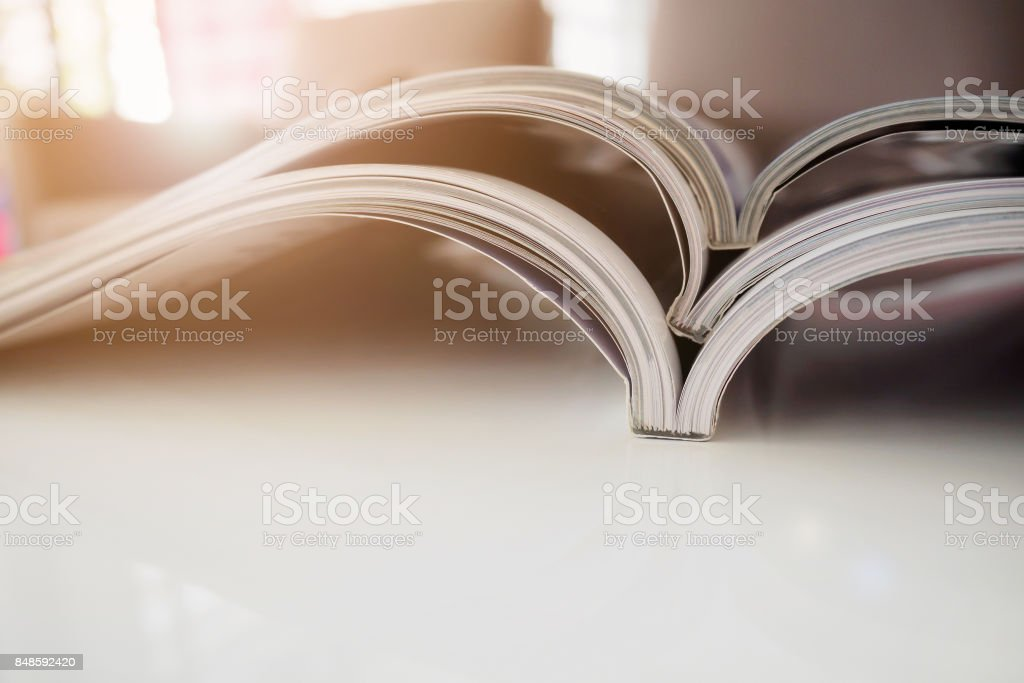 pile of magazines stack on white table in living room stock photo