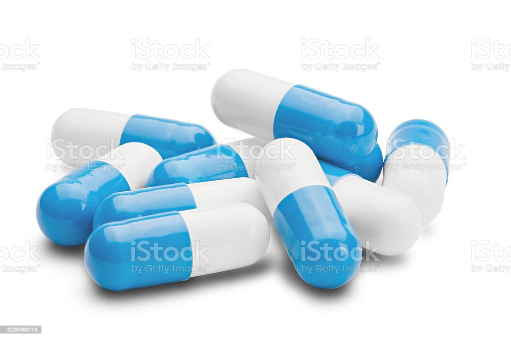 pile of medical pills blue and white on isolated background stock photo