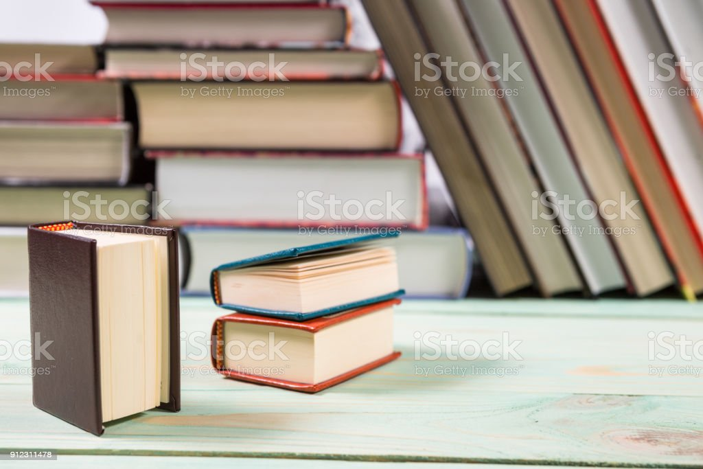 Pile Of Miniature Books On Wooden Background Stock Photo