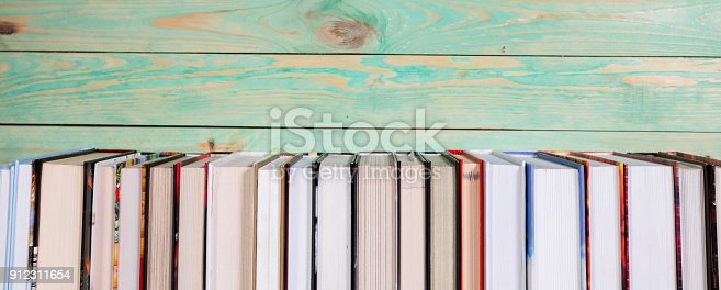 istock Pile of miniature books on wooden background 912311654