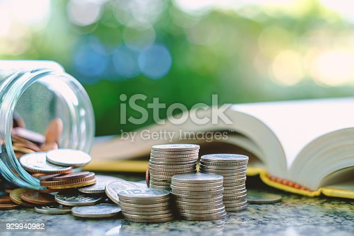 Pile of money coins in and outside the glass jar on blurred book and natural green background for financial and education concept