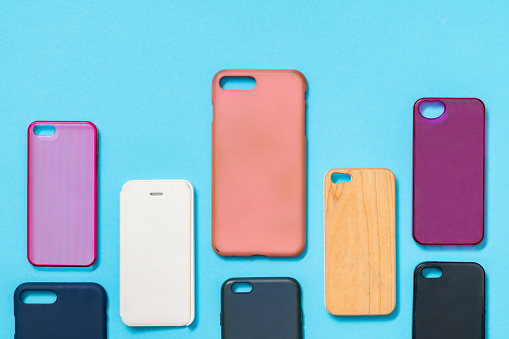Pile of multicolored plastic back covers for mobile phone. Choice of smart phone protector accessories on blue background. A lot of silicone phone backs or skins next to each other