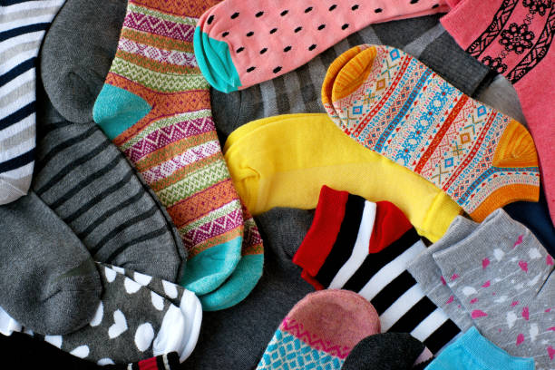 A pile of multi-colored socks. View from above. Many colorful socks form a textural background. Socks of different types and sizes. sock stock pictures, royalty-free photos & images