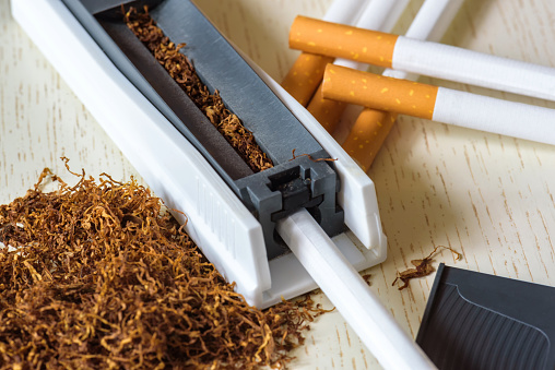 A Pile Of Natural Tobacco On A White Wooden Table And A Device For Manual Cigarette Making Smoking Nicotine Addiction Health Hazard — стоковые фотографии и другие картинки Без людей