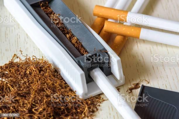En Hög Av Naturtobak På En Vit Träbord Och En Enhet För Manuell Cigarett Gör Rökning Nikotinberoende Hälsofara-foton och fler bilder på Aska