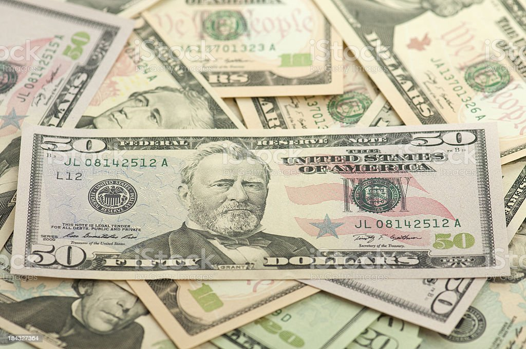 Pile of new American money fifty dollar bill on top stock photo
