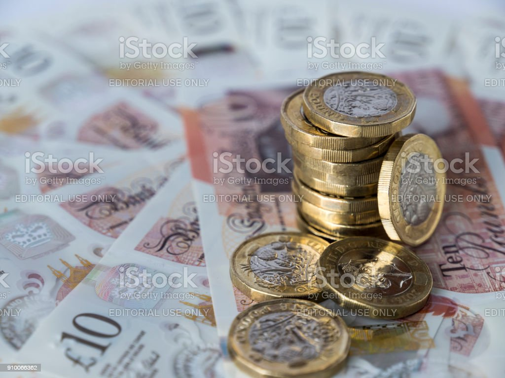 Pile of new pound coins on ten pound notes stock photo