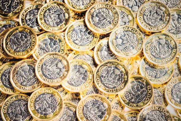 Pile of new UK One Pound Coins A collection of new British £1 coins. one pound coin stock pictures, royalty-free photos & images