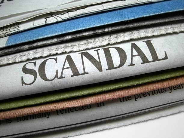 Pile of newspapers with scandal headline prominent stock photo