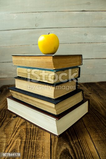 istock pile of old books and apple 927844178