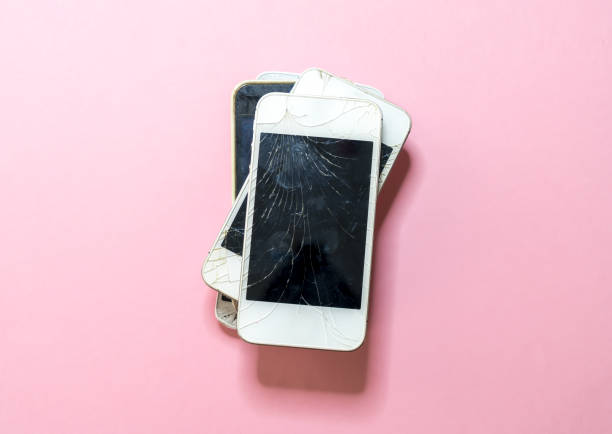 pile of old broken mobile phones with pink background stock photo