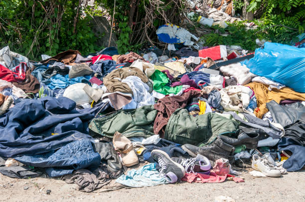 Pile of old clothes and shoes dumped on the grass as junk and garbage, littering and polluting the environment Pile of old clothes and shoes dumped on the grass as junk and garbage, littering and polluting the environment former yugoslavia stock pictures, royalty-free photos & images