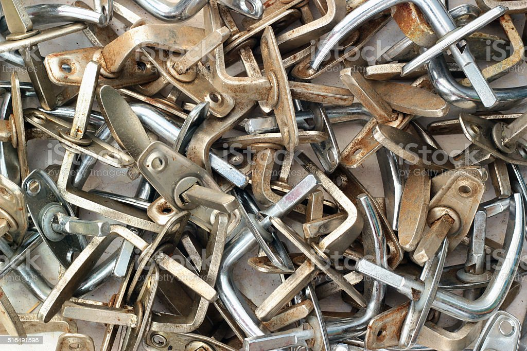 Pile of old dirty metal door handles stock photo