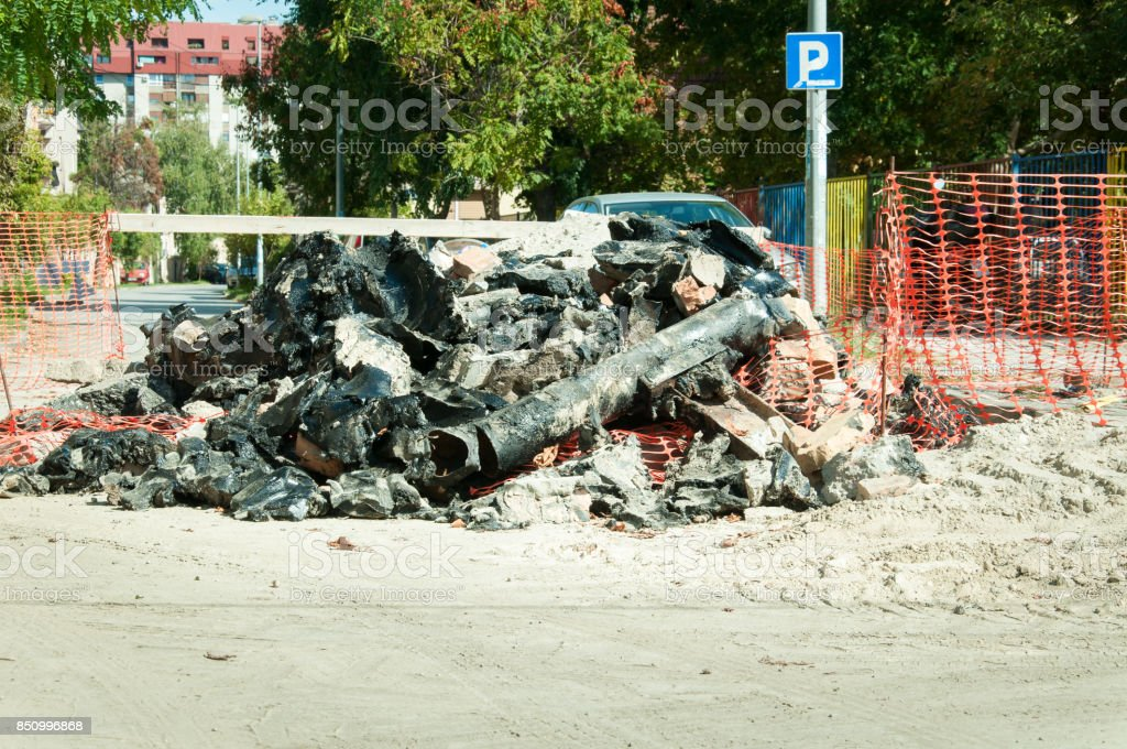 Pile of old pipes on the street excavated from the ground and replaced with new pipeline stock photo