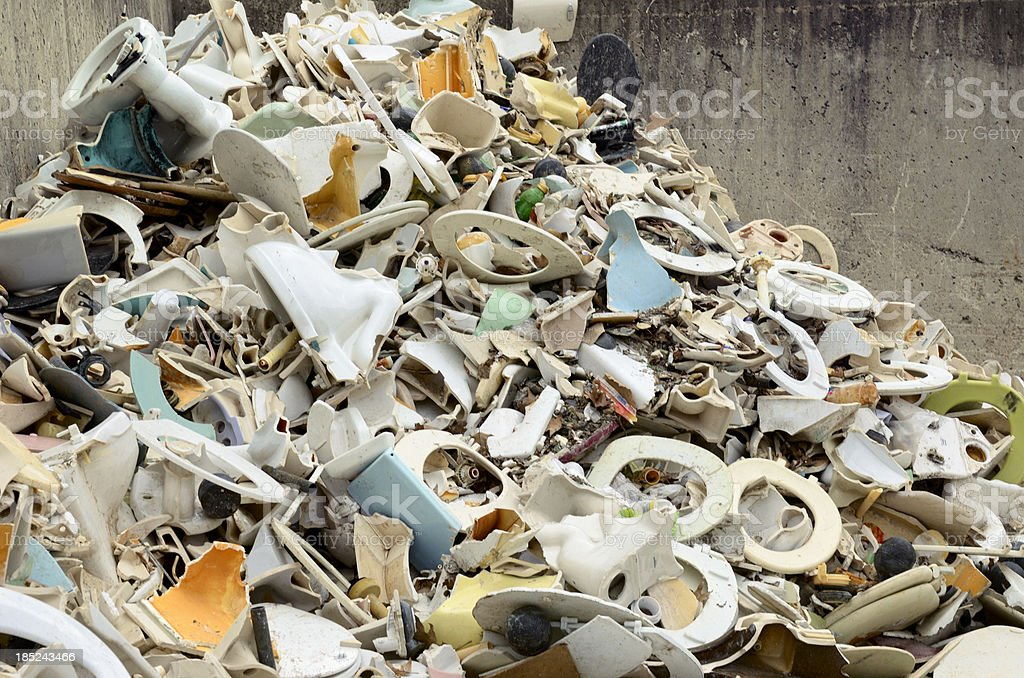 Pile of old toilets at garbage transfer station stock photo