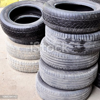 pile of old used car tires arranged in high piles.