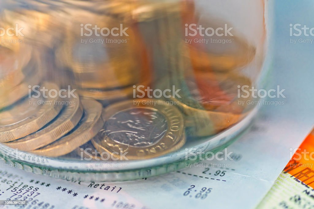 Pile of one pound coins in a jar on a receipt. stock photo
