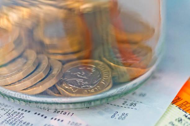 haufen von einem pfund-münzen in einem glas auf einer quittung. - gefüllte bon bons stock-fotos und bilder