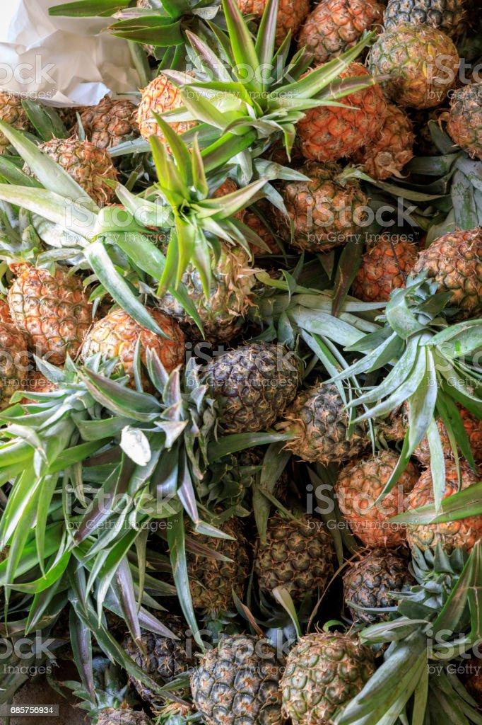 Högen av ekologisk ananas på marknaden royaltyfri bildbanksbilder