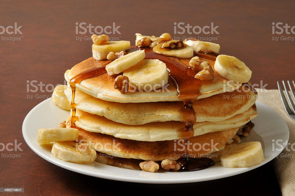 Pile of pancakes with banana and maple syrup on its top stock photo