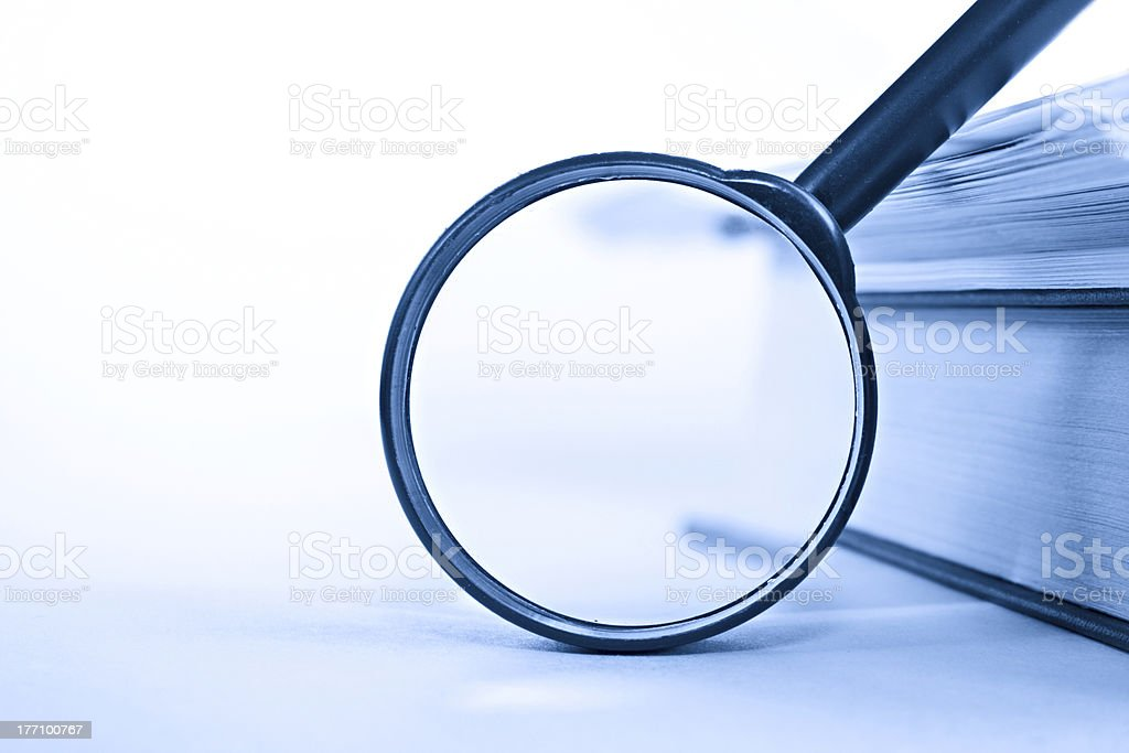 Pile of paper and a book through the magnifying glass stock photo