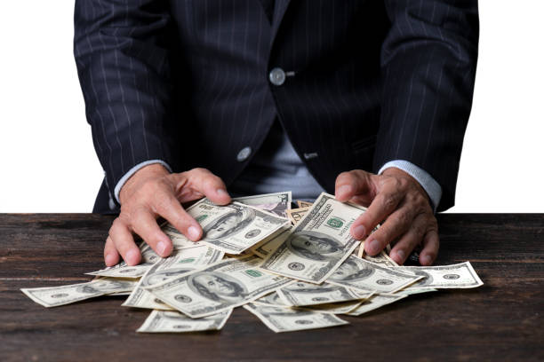 Pile of paper currency . Man hands in pinstripe suit sweeping pile of US dollar banknotes on old wooden table and white background,business concept. greed stock pictures, royalty-free photos & images