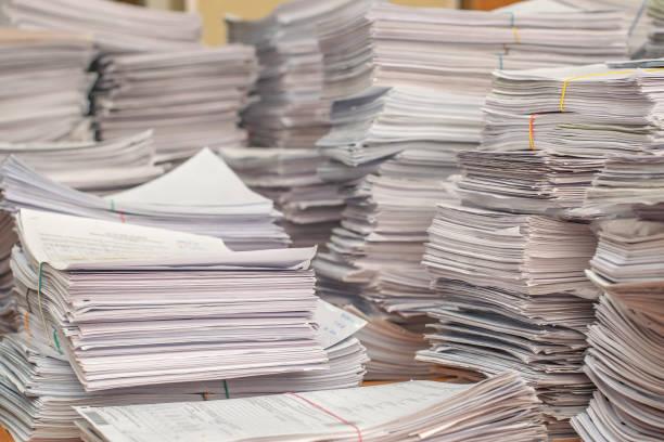 stapel von papierdokumenten im büro - haufen stock-fotos und bilder